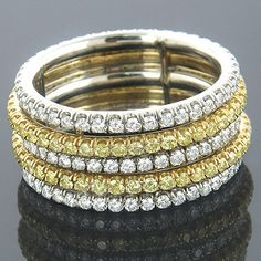 This absolutely magnificent 18K Gold & Platinum Natural Canary Diamond Eternity Ring from our unique designer diamond jewelry collection weighs approximately 12 grams and showcases a fantastic 2 tone design of 1.23 ctw sparkling white diamonds and 0.94 ctw dazzling natural canary yellow diamonds. Featuring a unique spinning diamond band design and the beauty of natural fancy yellow diamonds, this breathtaking diamond eternity band is simply irresistible.