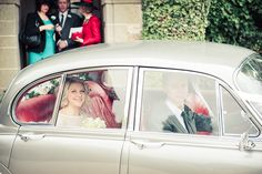 Photograph of Bride and groom in classic Jaguar wedding car by one thousand words wedding photographers in Dorset and Hampshire www.onethousandwords.co.uk