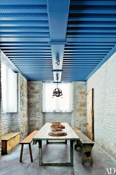 Farmhouse furniture stands beneath a beamed metal ceiling | archdigest.com
