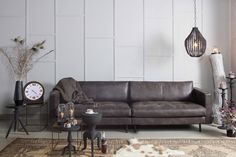Our Rodeo Classic leather sofa in Black, accessorised with the Funale hanging lamp, Motive rug, Brass metallic sidetable, the Ageless clock, Flare candle holder, Goblet and Slight sidetable and the Rocket stool by BePureHome #bepurehome #leather