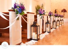 Pew lanterns, ribbons, and purple flowers. Flowers by The Blooming Gallery. Photography by Luke and Cat.