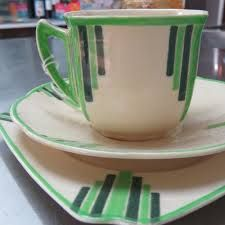 Doulton deco: unnamed earthenware tea trio in Pillar shape, D5211, Rd 764873, c1932 (pattern). Toned green straight lines, highlights and trim on very art deco Pillar square shaped cup and side plate.