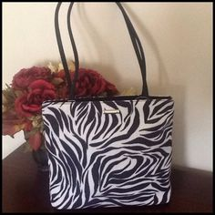 HOST PICKNine West Zebra Pattern Handbag. This bag is a soft body bag with black nylon handles and silver hardware. There is a three section interior which the middle section is a zipper compartment. One section has a side zipper the other does not. The handles measure 27 1/2 inches and the body is width 13 inches height is 10 inches. Nine West Bags