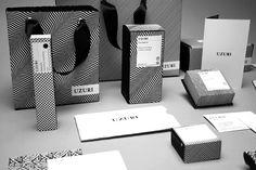 Photographie des packaging striés noir sur blanc des cosmétiques Uzuri.