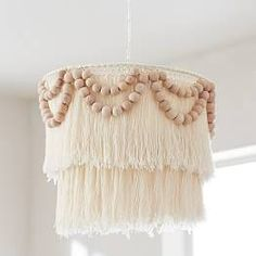 A little bit beachy, a little bit boho-chic, this handmade chandelier has tiers of cotton fringe accented with garlands of wooden beads. Handmade Chandelier, Beaded Chandelier, Chandeliers, Chandelier Ideas, Chandelier Lighting, Boho Lighting, Chandelier Shades, Deco Bobo, Idee Diy
