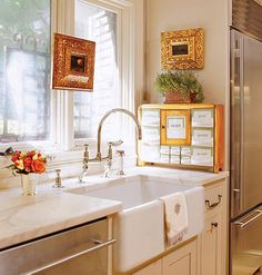 in the remodeled kitchen, a white farmers sink with creamy marble countertops and a stainless steel refrigerator