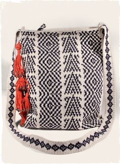 pima bag, handcrocheted in navy and cream kilim motifs and embellished with cherry-red, beaded tassels.