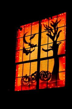 Pinner's halloween window - paper silhouettes    This is what the kids saw coming up my porch stairs. I drew and cut out all the paper silhouettes, put up orange holiday lights and put up the window shade.