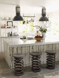 Open shelves, instead of upper cabinets, give a small kitchen in designer Ken Fulk's Napa Valley house an airy feel. The shelves and countertops are made of galvanized metal and the cabinetry is made from old fencing. Vintage truck springs, used as stools, were found at Artefact Design & Salvage. Fulk spotted the vintage industrial pendant lights at the Paris flea market.