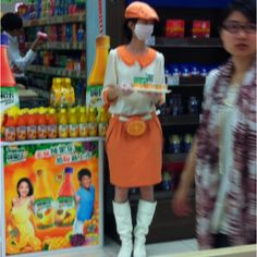 China. Orange Juice sampler in a supermarket.