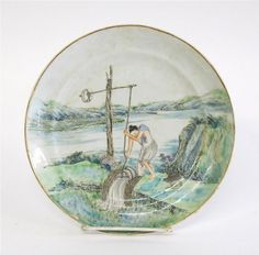 Chinese export porcelain famille verte plate with enamelled decoration of a man irrigating his rice field, late 18th century Centrally enameled to show a man irrigating a paddy field.