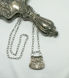 """This sweet filigree charm purse is attached to a 29"""" silver toned  chain.  No need for a clasp."""