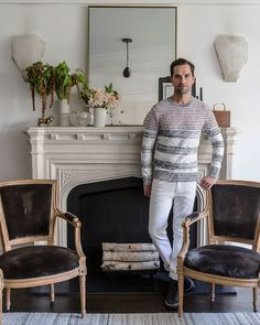 "Leifer in front of his redesigned fireplace. ""When I moved in, the whole thing was covered in a white glossy paint,"" he offers of the mantel. ""I had it finished to resemble limestone to match the large fireplace in the lobby, in keeping with the building's heritage."" The designer painted the interior stone a chic matte black. Rock-crystal sconces from Phoenix Gallery flank the setup."