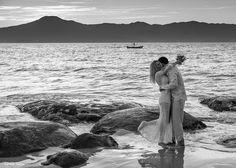 abraço gostoso em retrato preto e branco na praia da Daniela no costão. pescador ao fundo na baía norte de Santa Catarina
