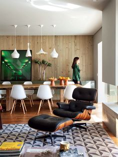 Patterns, bright white accents, wood-paneled wall, warm rustic wood dining table, black leather chair, and pops of yellow