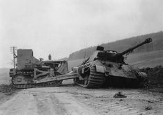 A D7 bulldozer of the 1st Engineer Battalion attempting to move this Tiger II off a road in Osterode, Germany on April 12, 1945.