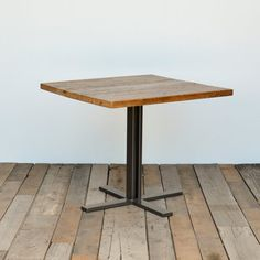 Small wood table made of century old lumber top and steel legs. We design and build custom reclaimed wood furniture for homes and commercial