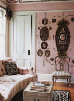 Pink room with some sort of doo-dads on the wall. What a sofa!