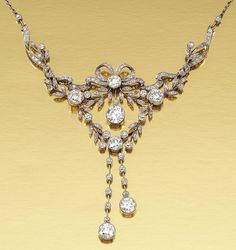 DIAMOND NECKLACE, CIRCA 1910.  In the Garland Style, designed at the front as an articulated open work frame embellished with tied ribbons and foliate motifs, set with single- and rose-cut diamonds, highlighted by seven principal circular-cut diamonds, on a fine chain, length approximately 380mm.