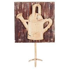 """Weathered wood wall hook with a metal garden tool-inspired accent.   Product: Wall hookConstruction Material: Wood and metalColor: MultiDimensions: 7.5"""" H x 4.75"""" W x 2.75"""" D"""