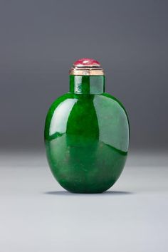 A Jadeite Snuff Bottle c.1780–1880 -- Jadeite; very well hollowed, with a flat foot and concave lip.   Stopper: tourmaline; gilt-silver collar