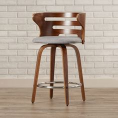 Featuring a wingback-inspired design, neutral-toned seat, and openwork back, this walnut wood swivel barstool effortlessly blends rustic appeal with midcentury modern style.