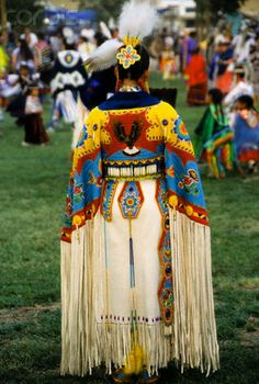 Chippewa-Cree woman dressed in beauiful beaded brain tanned traditional cape with a flying eagle design including long fringe. Marilyn Angel Wynn photography