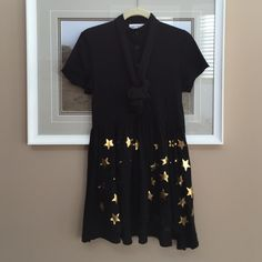 """Wildfox Black & Gold Star School Girl Dress Authentic Wildfox Gold Star Dress. Hi-Low Hem. Super Soft Flowy Material. Long Neck Tie. No rips/stains - what I would consider Excellent Condition. Marked Size Sm but fits up to a Med (ref I'm 5'0"""" & 120lbs with a34bust) Open to All Offers comes from a nonsmoking with fluffy furkids home Wildfox Dresses High Low"""