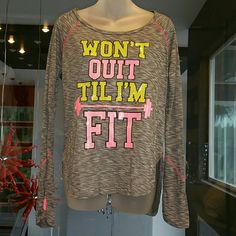 """WON'T QUIT TIL' I'M FIT"" NEW Get a head start on your new year's resolution and motivated with this ""Won't quit til' I'm fit"" shirt. Fabulous gray color with vibrate colors of pink and yellow!! A fabulous addition to your workout wardrobe!! This top is longer in the back then front and offers sexy side slits, seen in pic2, also finger hole for your thumb pic#4   Only 1 available! Brand new, no tag 50%polyester  50%rayon Length in front approx. 25"" Length in back 27"" Tops"