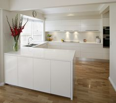 u shape kitchen - with horizontal wood/vinyl flooring. Widens the room.