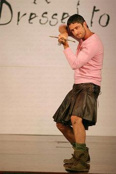 gerard butler in a kilt and wonderful pink shirt.