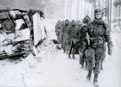 A paratrooper of the 82nd Airborne Division leads a column of German prisoners past a disabled Stug IV in the Ardennes...