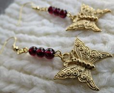 50% of proceeds from the sale of these butterfly earrings benefit a non-profit animal rescue group in Burlington NC. Antique Gold Butterfly Charm and Red Garnet by StephieGknits, $12.00