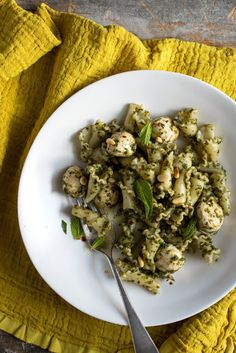 NYT Cooking: In this green pasta dish, basil, mint, Parmesan and garlic are blended into a smooth pesto-like sauce, then tossed with pasta, creamy mozzarella and crunchy pine nuts just before serving. Marinating the mozzarella in some of the sauce as the pasta cooks imbues the mild cheese with flavor, and allows it to start softening so it melts in contact with the pasta. Serve thi...