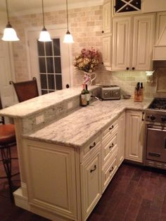 My DIY #kitchen. Two tier peninsula, Viking range, stools from wayfair.com. Antique white grainy counter tops and off white and slightly distressed cabinets.