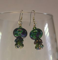 Handmade Clear Lampwork Beads with Transparent Frits in Green, Purple and Blue. Made with silver craft wire, silver plated earwires, fire polished rondelles, and purchased bellflower beads.