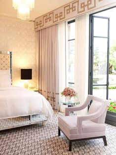 Nothing says elegance like floor-to-ceiling window treatments in a neutral tone. Designer Jamie Herzlinger gave this grand bedroom a Hollywood Regency look with dramatic ivory draperies adorned with a gold Greek key design on the valance.