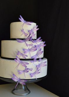 So cute! Edible purple dragonflies on a layered white wedding cake #weddingcake #cake #wedding #dragonflies #purple