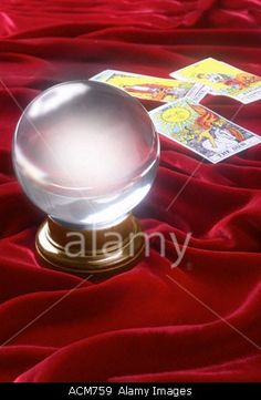 Crystal ball on red velvet with Tarot cards Stock Photo
