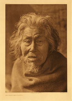 """Oldest man of Nootka, 1915. Photogravure. Curtis Caption: """"This individual is the most primitive relic in the modernized village of Nootka. Stark naked, he may be seen hobbling about the beach or squatting in the sun, living in thought in the golden age when the social and ceremonial customs of his people were what they had always been."""""""