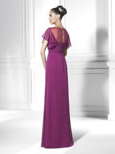 Vestido de madrina confeccionado en chiffon de seda y color borgoña. El cuerpo está elegantemente drapeado y con el detalle característico de la flor. La transparencia sobre el pecho, se une con unas flamencas mangas y sus ondulaciones.
