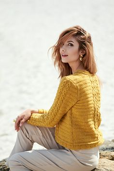 Elegant chain link cables framed by a welt pattern adorn this casual sweater. It is knitted straight from the bottom and up in parts with extra ease for comfort. Spindrift, a fine heathered wool was chosen for its lightness and color. The round neck makes it easy to wear over a crisp shirt or your favorite t-shirt.