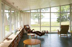 La casa di Bruno Mathsson (1907-1988), designer e architetto svedese, è immersa nella natura in perfetto stile scandinavo. Il soggiorno ha finestre a tutta altezza per godere della vista sul fiordo e per catturare quanta più luce naturale possibile. Minimale ma super accogliente, è arredato con mobili originali come la famosa chaise-longue Pernilla (a sinistra e di spalle) disegnata proprio da Mathsson nel 1934.