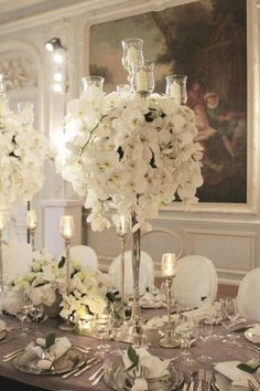 Tall silver candelabra with white orchids....these are the flowers we have for our wedding and NOW I reallyyyyyy want a candelabra!