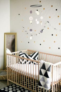 Girl's nursery featuring black and gold polka dot wall decals