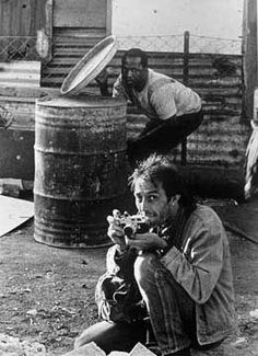 This photo shows Kevin Carter taking photos next to a man hiding in the middle of gun fire.