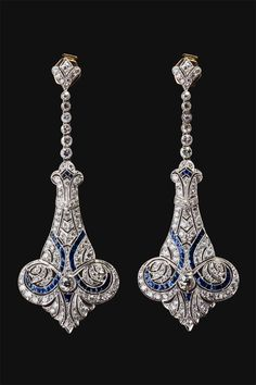 Precious earrings in silver by the late Art Nouveau style, with decorative motifs in early art deco setting of diamonds and blue sapphires. English, 1910.