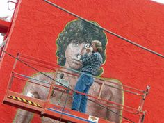 """""""Yep, That's Him"""" Artist Rip Cronk refreshes his famous mural of Jim Morrison, located on a beachside building at Venice Beach in the summer of 2012 while using Morrison's famous """"Lion Shoot"""" photo for reference. Venice Beach was the location of the re-meeting of Morrison and Manzarek in 1965 where """"The Doors"""" were born."""""""