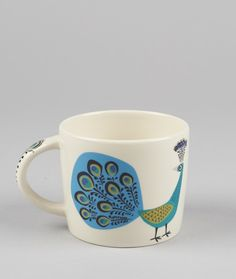 Hannah Turner Peacock Mug: The Hannah Turner peacockrange is both elegant and stylish. Each product is handmade andembellished with beautifully illustrated designs of elegant strutting peacocks.Set the world to rights over a goodcup of tea. This mug is a lovely size and shape for a proper brew.  Hannah Turner started her business in 1991 after a sell out degree-show. Hannah works out of a studio based in the back garden of her home in Bristol, selling her amazing products to companies…