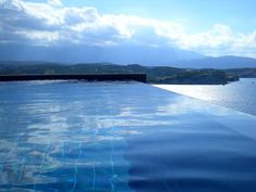 It has a salt water infinity edge pool with a glass wall and tiles to match the surroundings so it completely blends in.